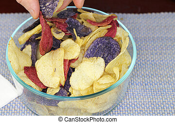 Fingers Choosing Red, Purple and Yellow Potato Chips