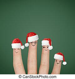 Fingers dressed in Santa hats. Happy family celebrating...
