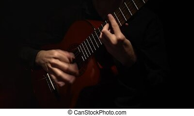 Fingers fingering the strings on the guitar . Close up -...
