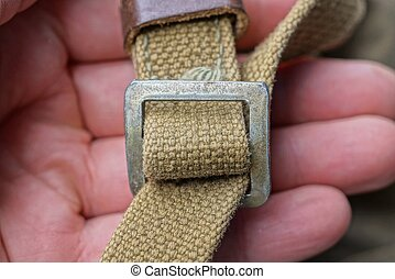 fingers hold a gray metal carbine on an old green harness