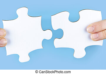 Fingers holding jigsaw puzzle pieces