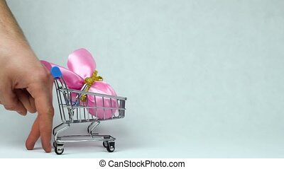 Fingers like human legs roll a toy shopping cart with...