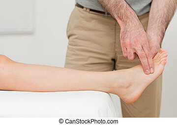 Fingers of a physiotherapist touching a foot in a room