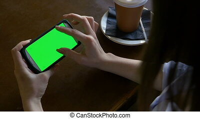 Fingers of a woman making zoom in and out gestures on smart phone with green screen in a cafe