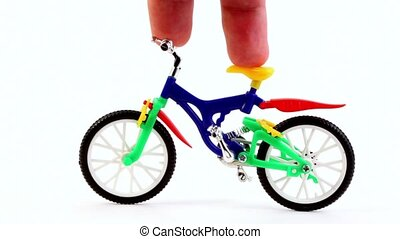 Fingers on toy bike, rotates handlebars, and then ride away