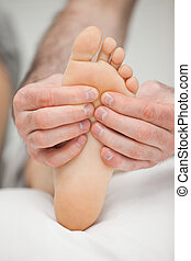 Fingers palpating the sole of a foot