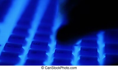 Fingers press buttons of keyboard with blue backlight in dark