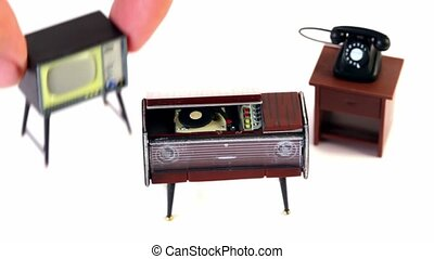 Fingers takes toy vintage phonograph, phone and tv set