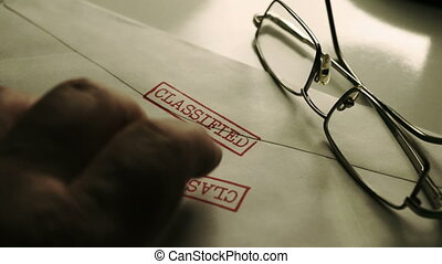 Fingers tapping on classified document