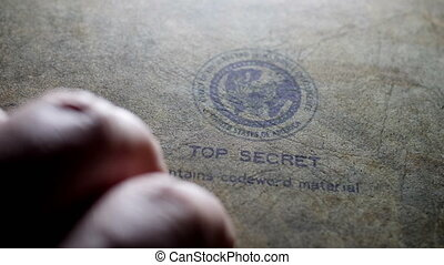 Fingers tapping on top secret document