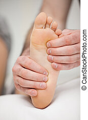 Fingertips touching the sole of a foot in a room