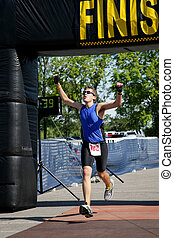 Finish Line - Triathlete crosses the finish line.