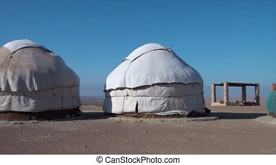 Finished and unfinished yurts - A wide panning shot showing...