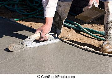 Finishing Concrete Sidewalk - Concrete finisher uses a float...
