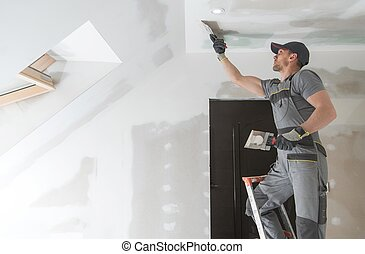 Finishing and Patching Drywall Walls by Caucasian Remodeler in His 30s. Construction Industry.
