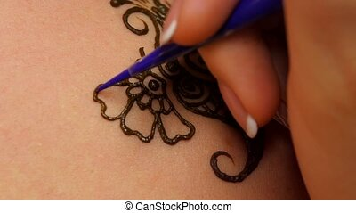 Finishing process of applying mehendi on the female back -...