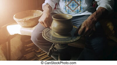 Finishing the Clay Jug - Potter cuts clay jug from the...