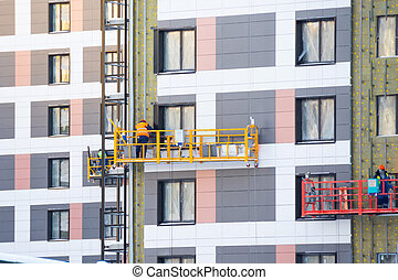 Finishing the facade of residential buildings by workers on the construction elevator, completion of construction.