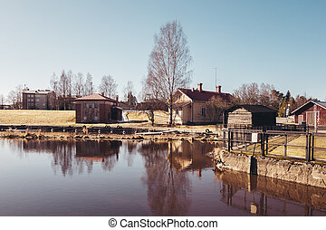 Finland Forssa, Loimijoki river at Kuhalankoski, a small boats marina at summer and with a dam on it's side. On a spring day when all snow has almost melted