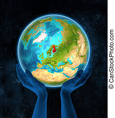 Finland on Earth in hands - Finland in red on globe held in...