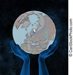 Finland on political globe in hands - Finland with flag on...