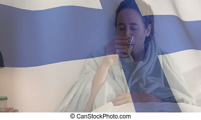 Animation of Finnish flag waving over a sick Caucasian woman lying in bed coughing taking medicine. Global coronavirus pandemic concept digitally generated image.