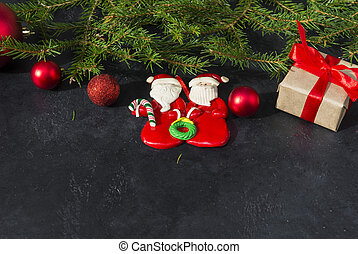fir branches, 2 toy Santa Claus, gift box tied with red ribbon, red balls on black background, Christmas