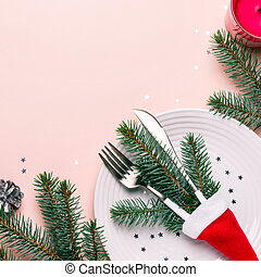 Fir branches and cutlery in Santa hat on pink background. Christmas table setting