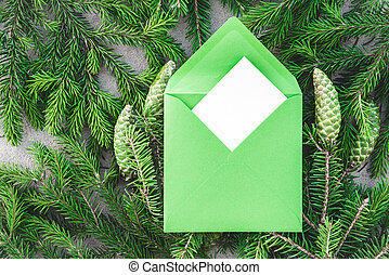 Fir branches and green envelope with blank greeting card