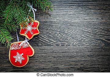 Fir tree branch gingerbread cookie on wooden board