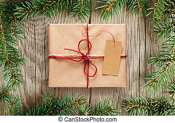 Fir tree branches and gift box with tag on wooden background