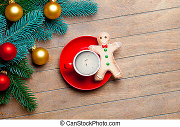 fir tree branches, cup of coffee, gingerbread man and colorful baubles on the wonderful brown wooden background
