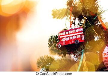 Fir tree decorated with toy double decker bus and light...
