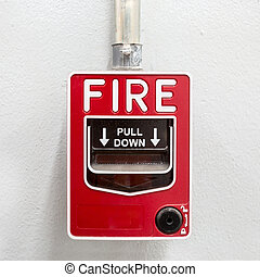 Fire alarm on white wall used to report a fire on the...