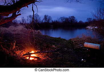 Fire and on river bank - Fire and tourist backpack on river...