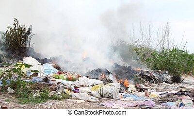 Fire at the garbage dump. Burning garbage, ecology in...