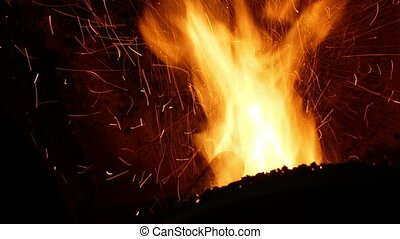Fire burn pellets with spruce sawdust into the delivery strew bio wooden pallets to industrial modern boiler, sparks fly out and flames fire detail , biofuels made from compressed biomass fuel