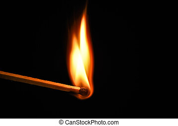 Fire burning on matchstick. Isolated on black background.