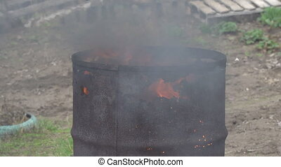 Fire burns in an old rusty barrel