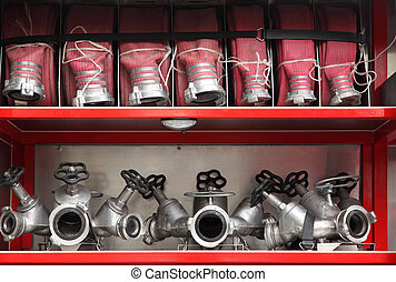 Fire cocks and hoses accurate organized inside big red fire...