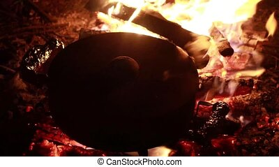 Boiling pot cooking dinner on embers of a campfire during night time.