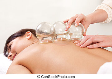 Fire Cupping - Acupuncture therapist removing a fire cupping...