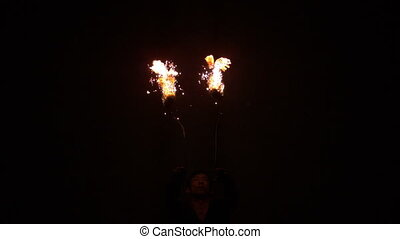 Fire dancer making trails in the dark in slow motion