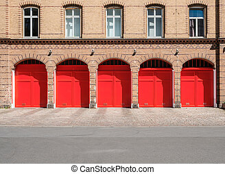 fire department builidng facade with red doors and empty street