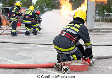 Fire department training - Firefighters spraying water in...