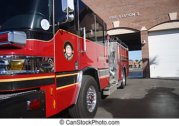 Red and black fire engine parked in front of Fire Station number 3. Image shows truck front and driver side as well as the front of the fire station.