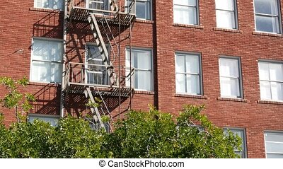 Fire escape ladder outside residential brick building in San...
