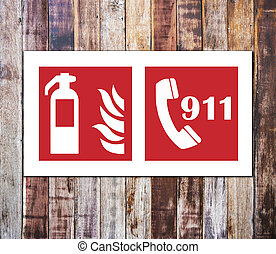 Fire extinguisher sign and 911 emergency isolated on wooden wall