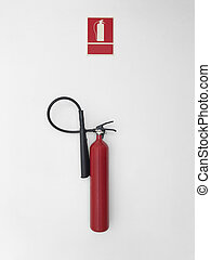 Fire extinguisher with sign alarm on a white wall