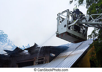 Fire fighter extinguishing flames on burning roof
